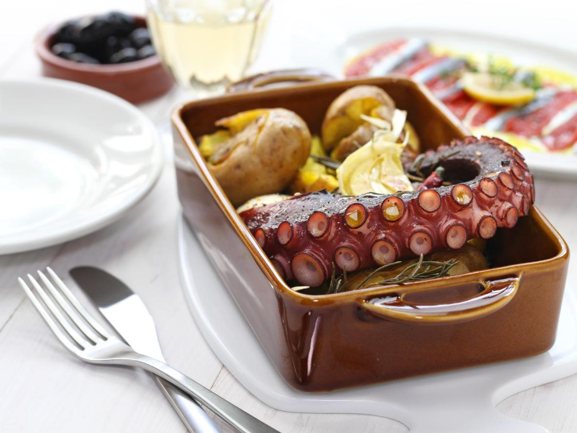 Un plato de pescado flotando en aceite de oliva y empapado en sabor.