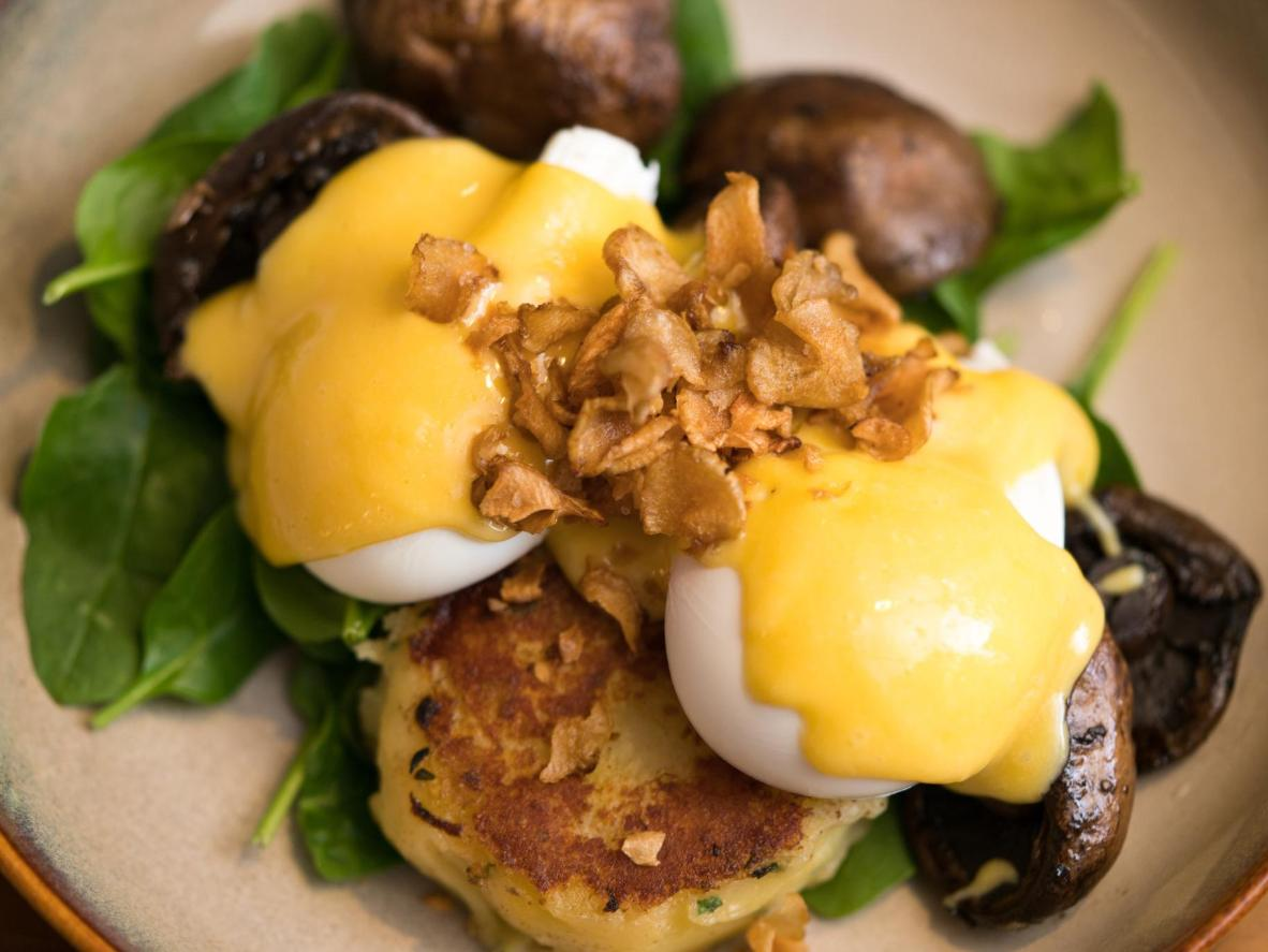 Portobello mushroom and Gruyere potato rosti at the Grain Store, with poached eggs, spinach leaves, and hazelnut hollandaise