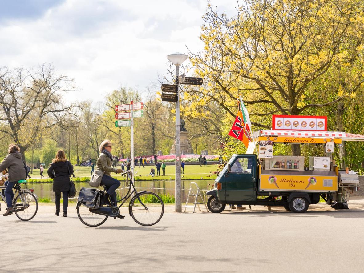 Cyclists pass by an ice cream truck in Vondelpark