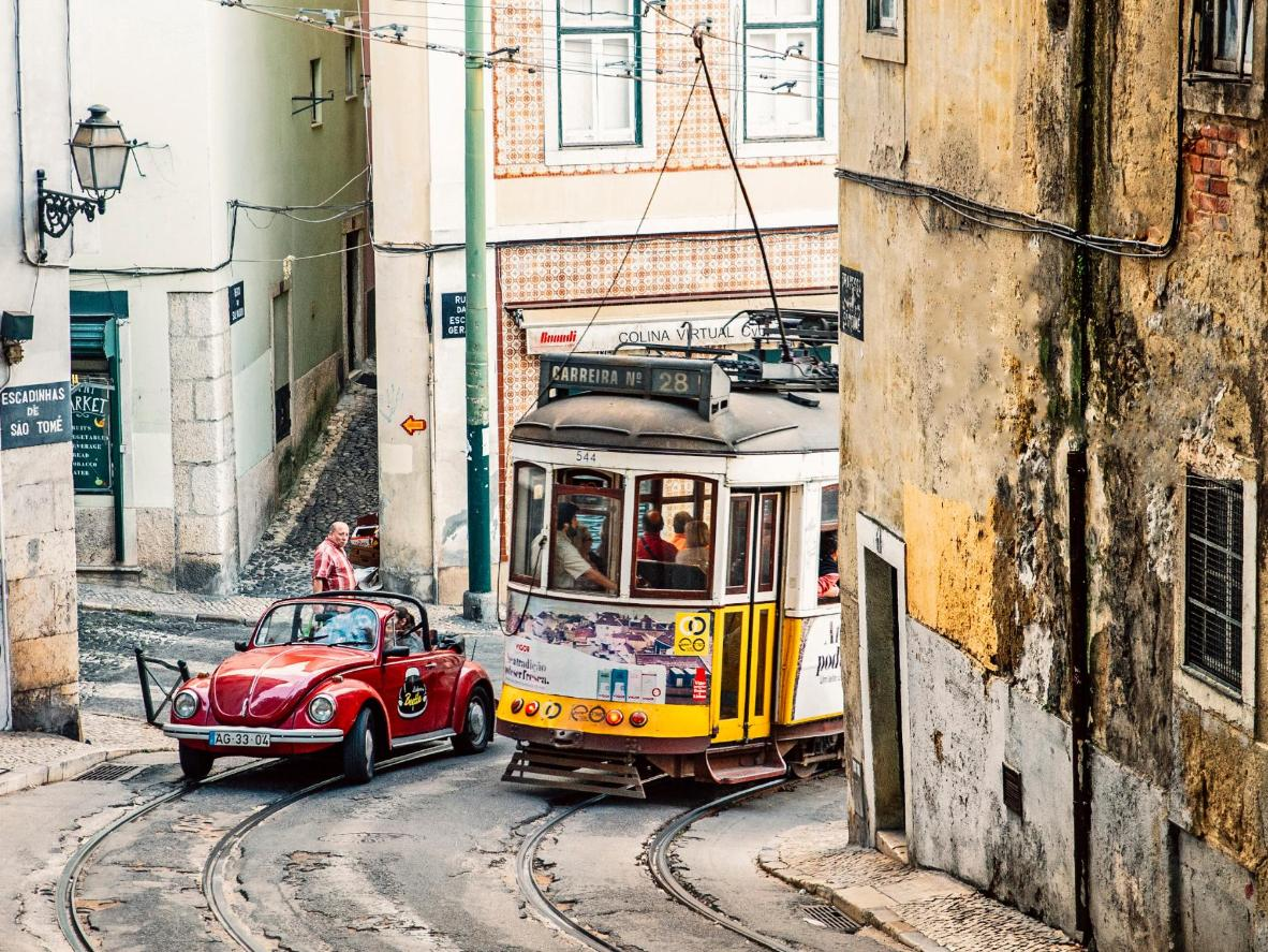 The famous Tram 28 navigates a sharp turn in the Alfama district