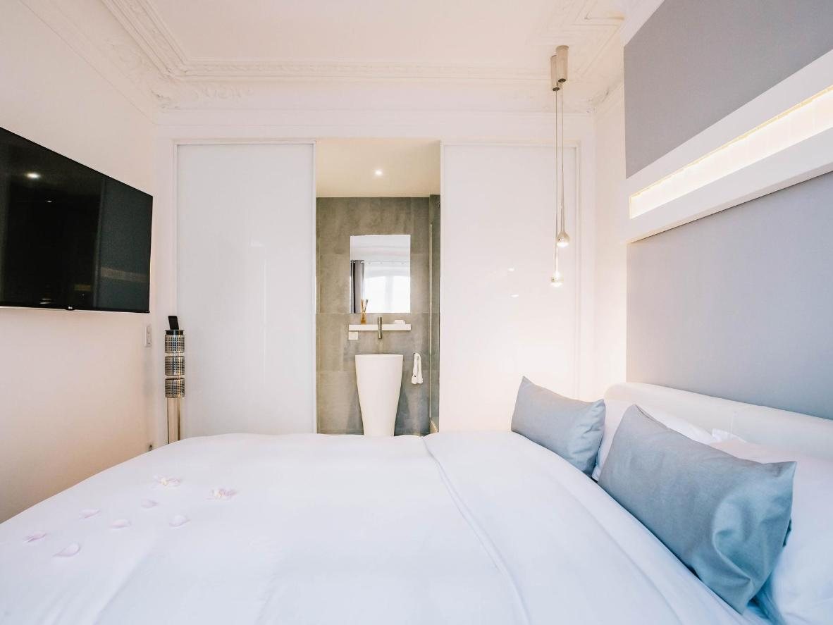 El dormitorio blanco se conecta con el baño renovado de color gris pizarra.