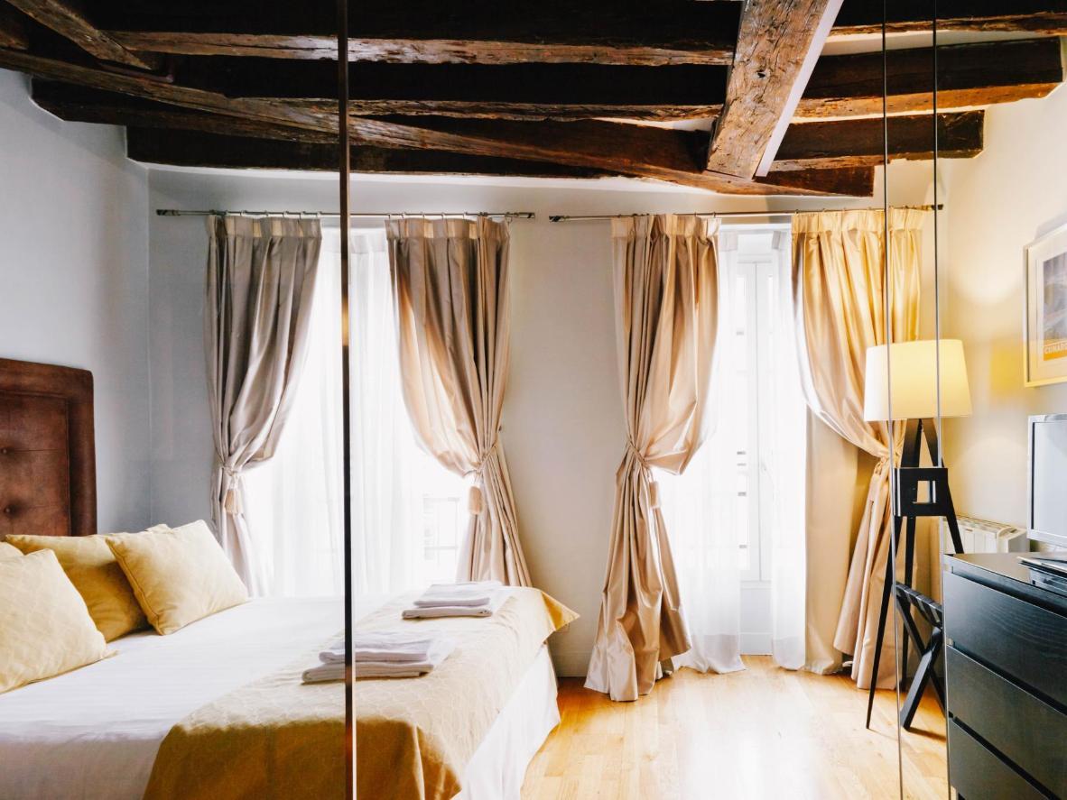 Las vigas de madera expuestas y los detalles en amarillo mostaza calientan la habitación.