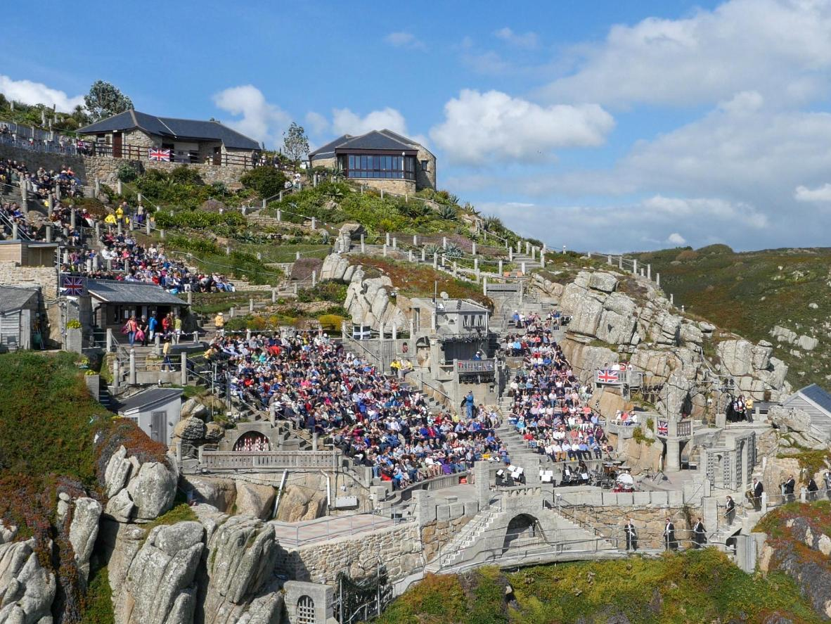 The Minack theatre was carved into the granite cliffside hundreds of feet above the Cornish surf. Image credit: Minack Theatre.