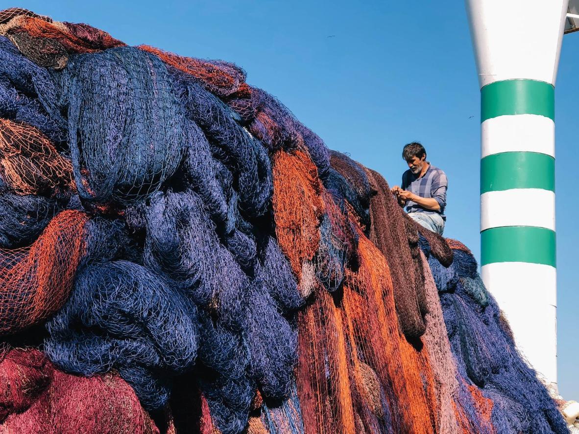 Vea si puede ver a los lugareños remendando sus redes de pesca en la costa de Sariyer