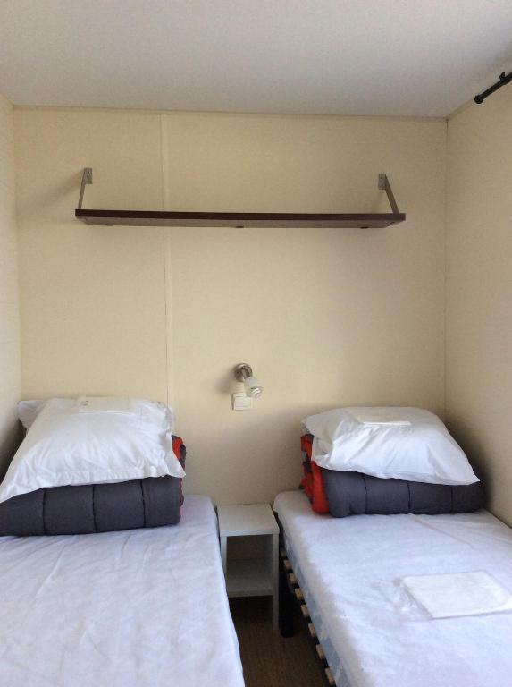 Un ou plusieurs lits dans un hébergement de l'établissement Camping le Mont Joli Bois