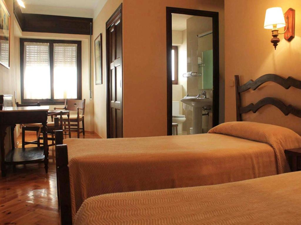 A bed or beds in a room at Hostal Rita Belvedere