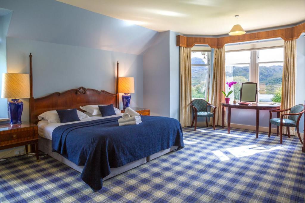 A bed or beds in a room at Glencanisp Lodge