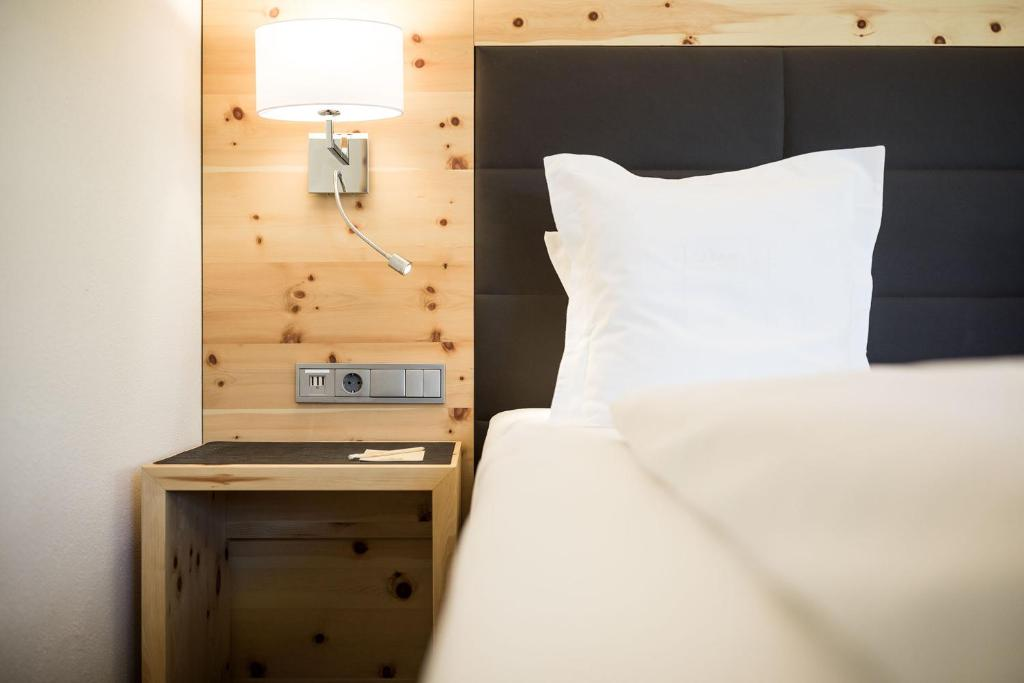 A bed or beds in a room at Cappella Natura Vitalis Hotel