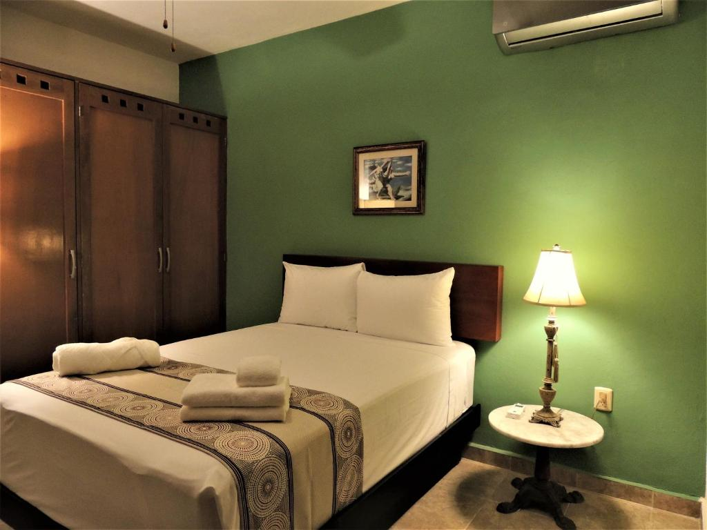 A bed or beds in a room at Maya Suites By LHMG