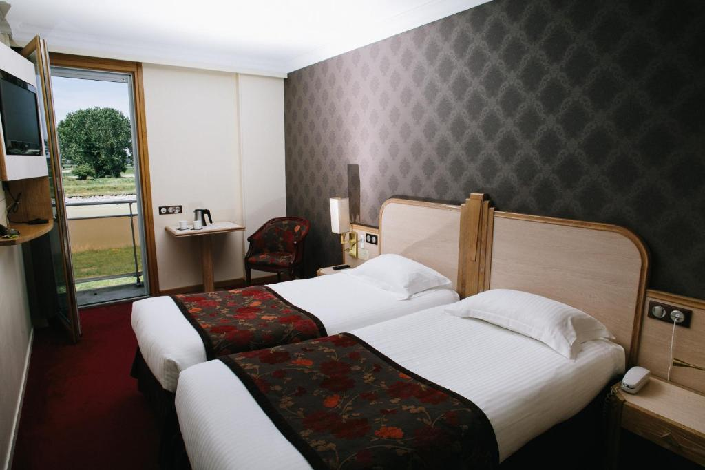 A bed or beds in a room at Le Relais Du Roy