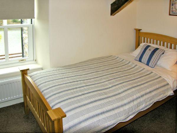 A bed or beds in a room at Tyn Llwyn, Talsarnau