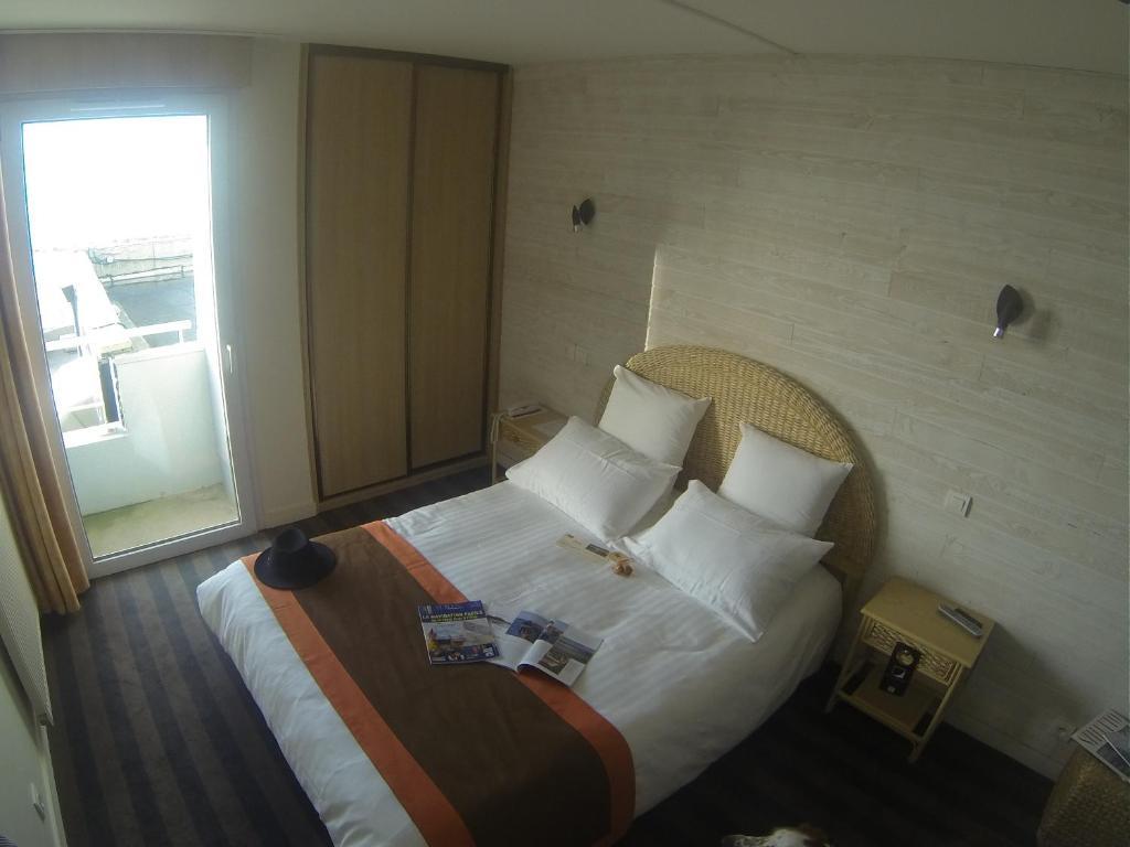 A bed or beds in a room at Hôtel Restaurant L'Empreinte