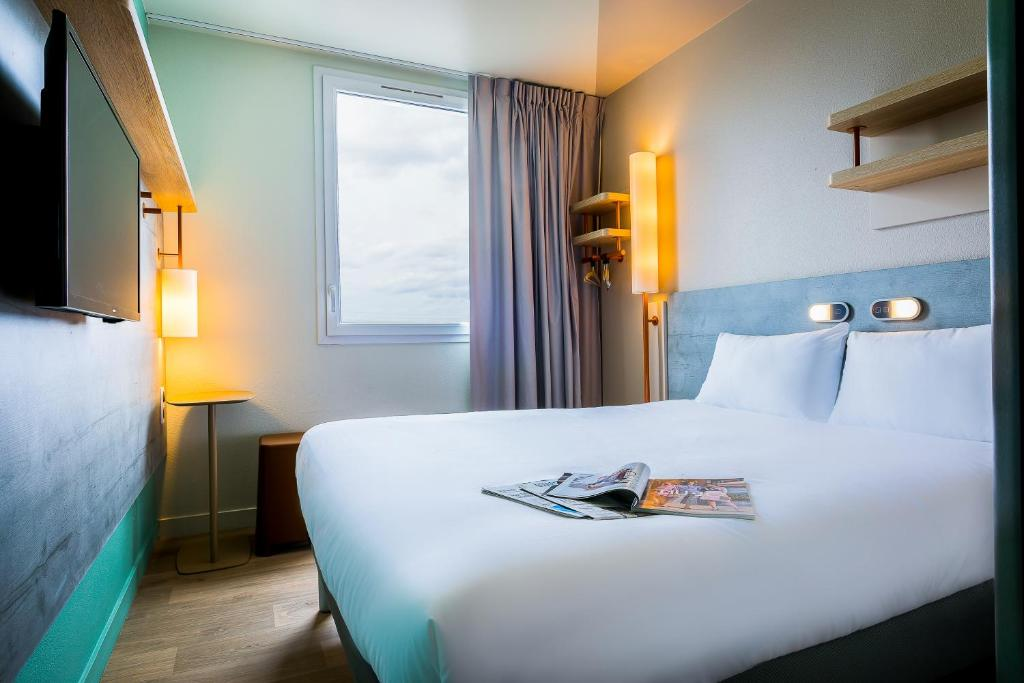 A bed or beds in a room at ibis budget Senlis