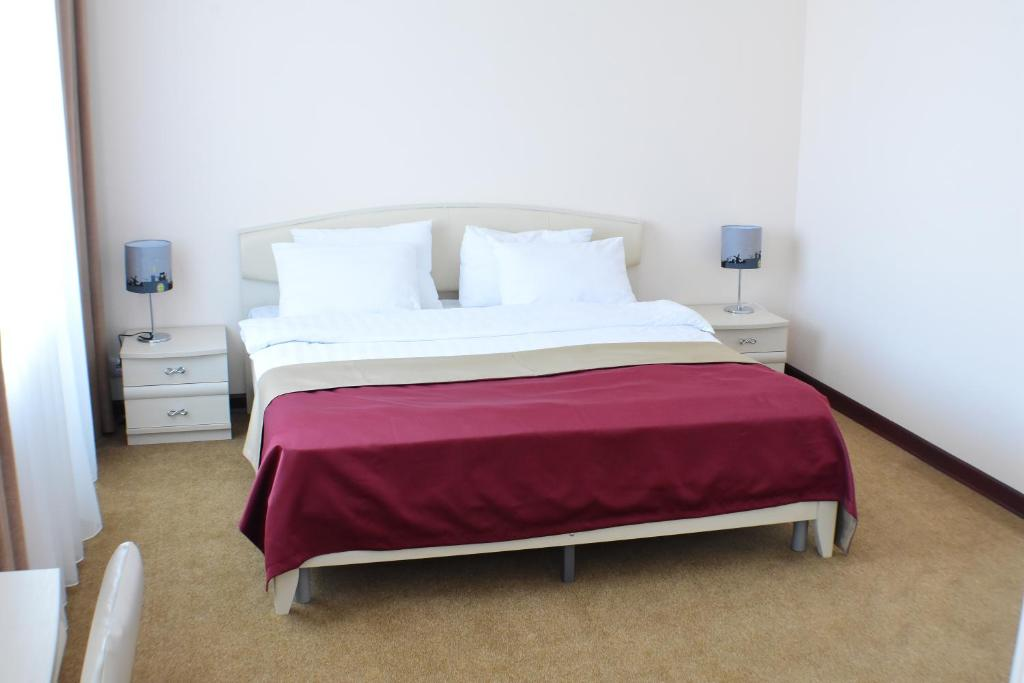 A bed or beds in a room at Magas Hotel