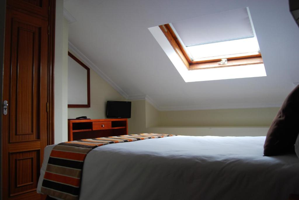 A bed or beds in a room at Hotel Anunciada