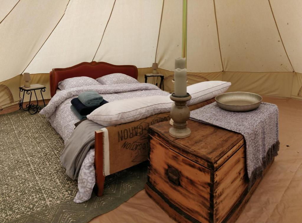 A bed or beds in a room at La Fortinerie Glamping Bell Tent