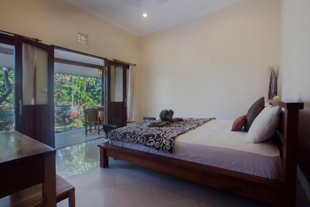 A bed or beds in a room at Nyoman Guest House Ubud