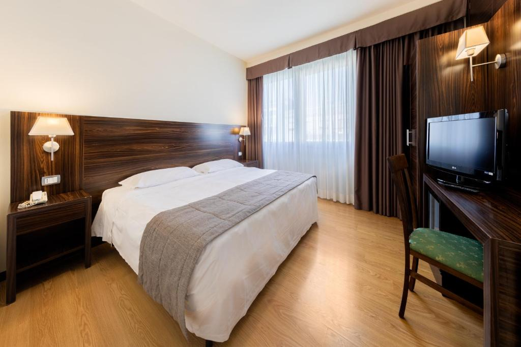 A bed or beds in a room at Quality Hotel Delfino Venezia Mestre