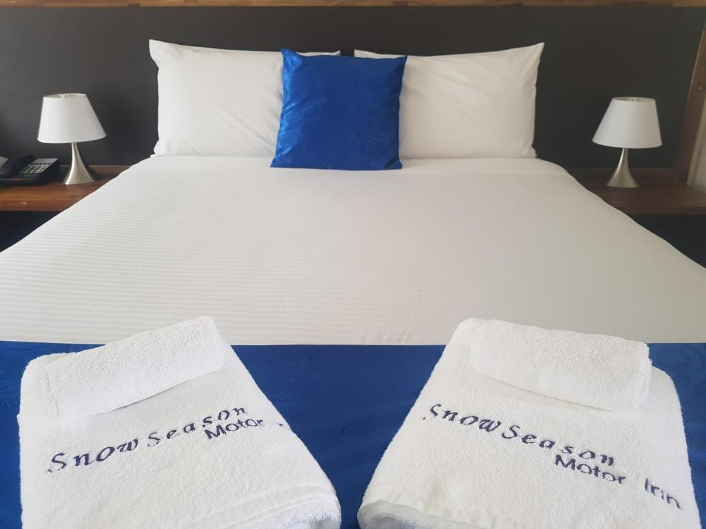 A bed or beds in a room at Snow Season Motor Inn