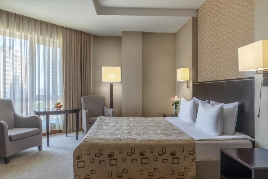 A bed or beds in a room at Qafqaz Point Hotel