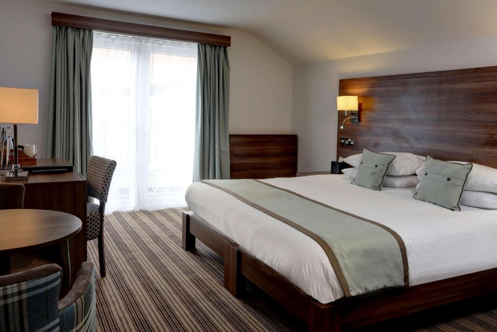A bed or beds in a room at Best Western Brome Grange Hotel
