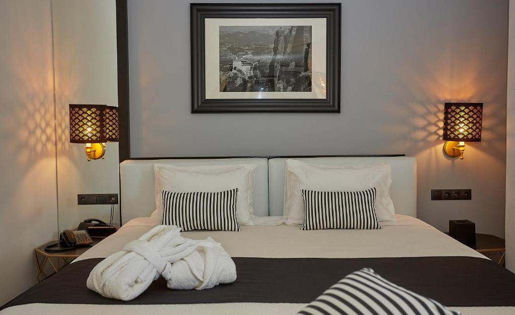 A bed or beds in a room at Athenian Riviera Hotel& Suites
