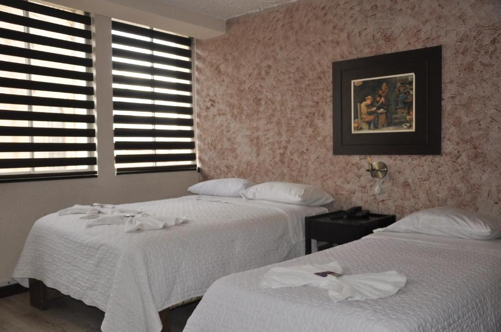 A bed or beds in a room at Hotel Catedral Cuenca