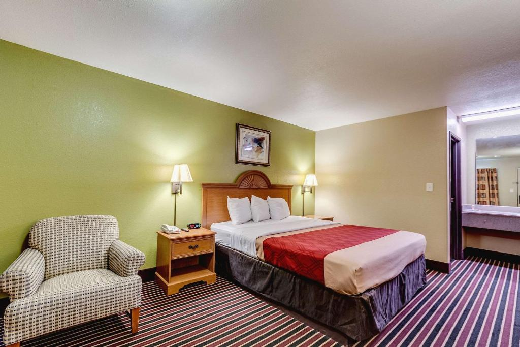 A bed or beds in a room at Econolodge Lake Charles