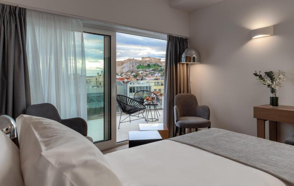 A bed or beds in a room at Elia Ermou Athens Hotel