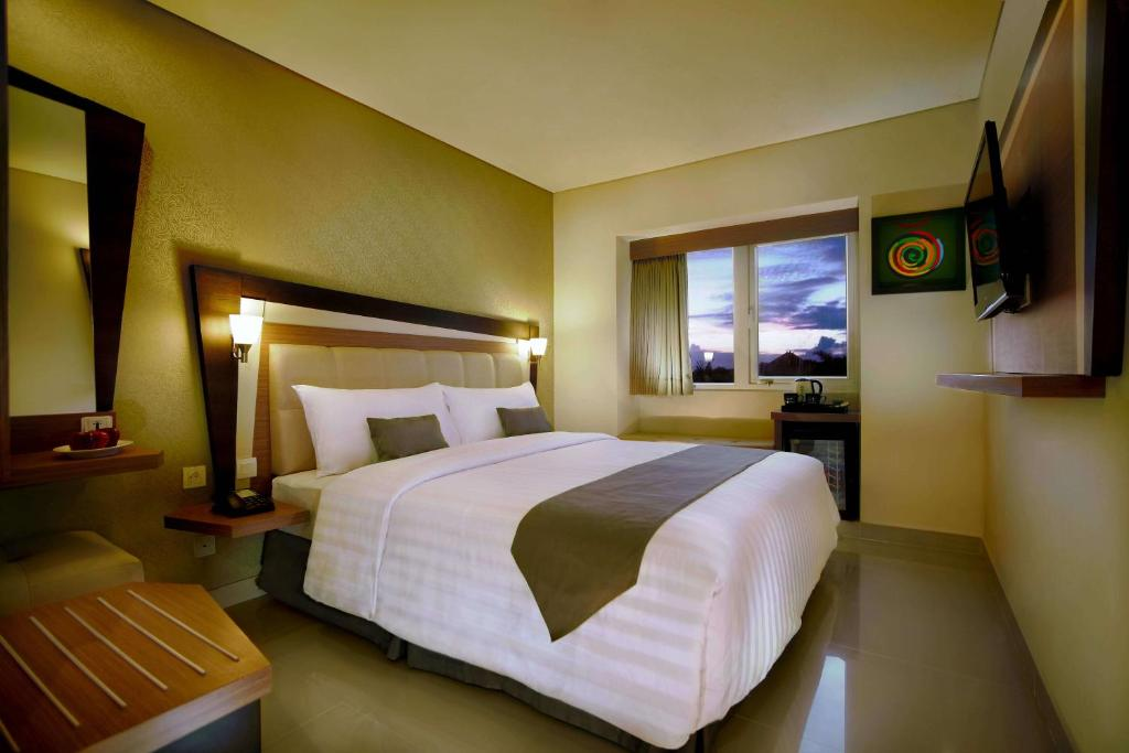 A bed or beds in a room at Hotel Neo - Kuta, Jelantik