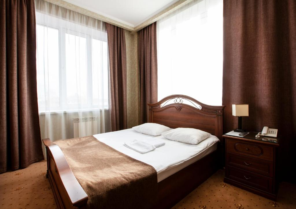 A bed or beds in a room at Hotel Lazurny Bereg