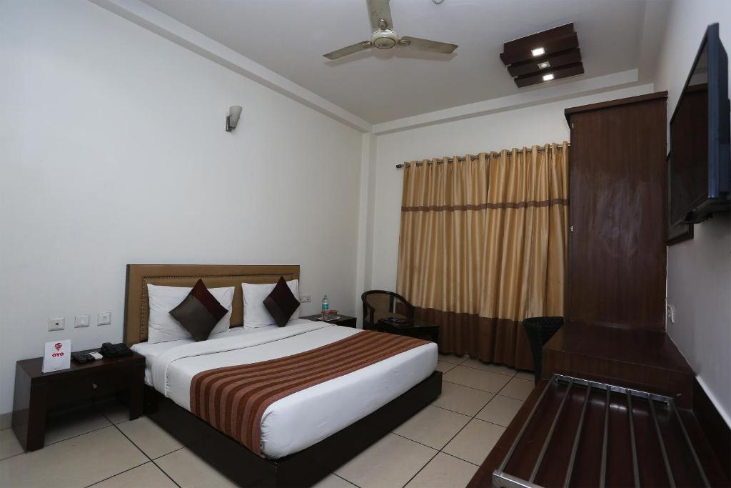 A bed or beds in a room at OYO 1391 Hotel Pushpa Vilas