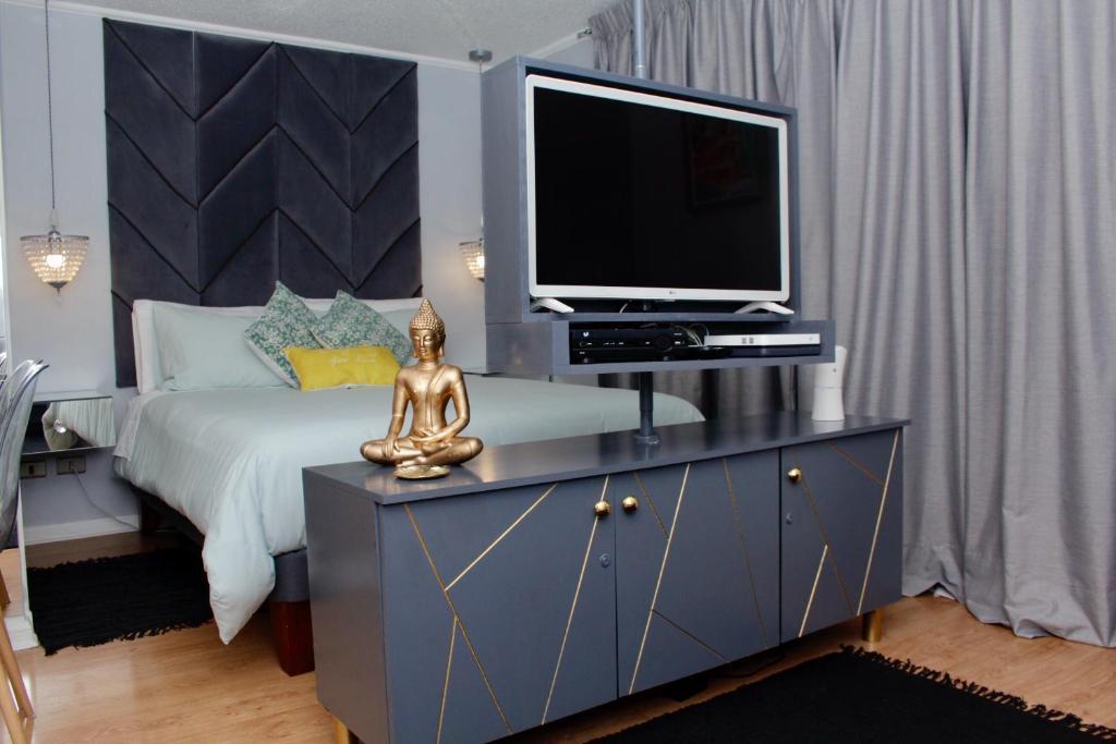 Una televisión o centro de entretenimiento en Go Santiago Apartments