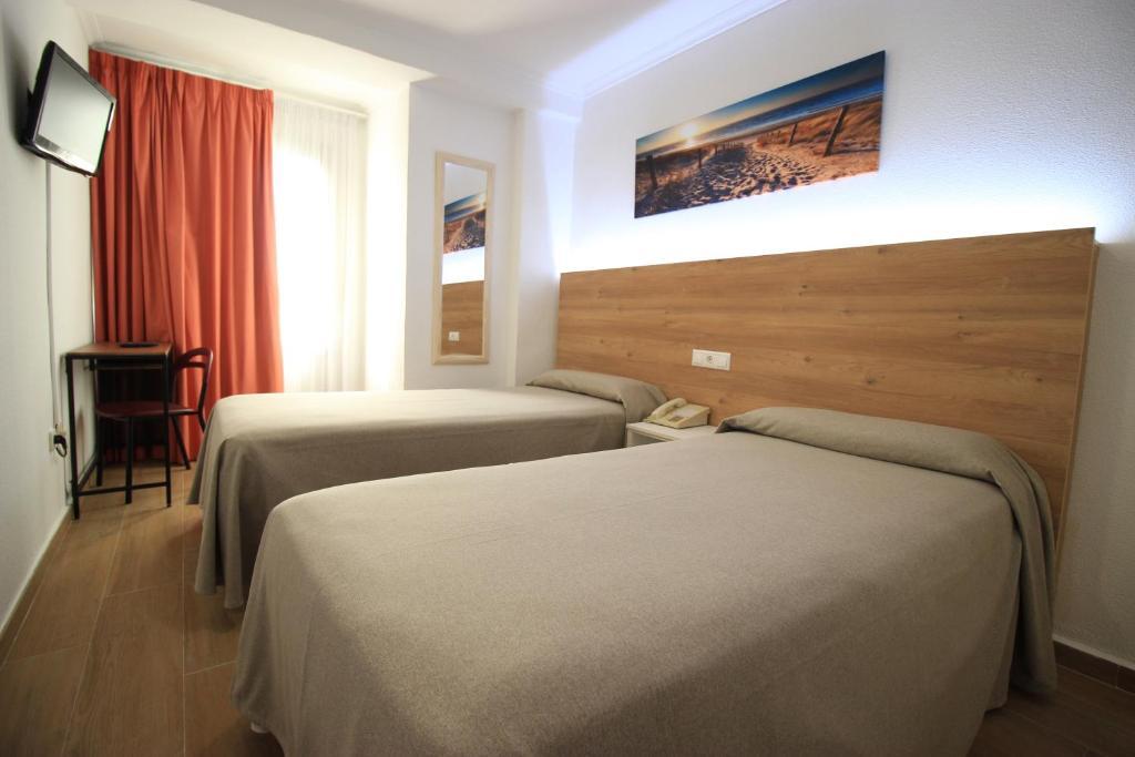 A bed or beds in a room at Hostal Pensimar
