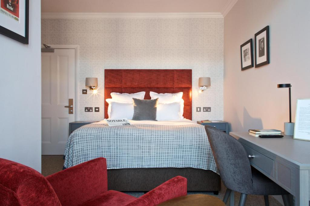 A bed or beds in a room at 54 Queen's Gate Hotel