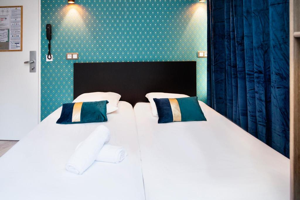 A bed or beds in a room at Résidence AURMAT - Aparthotel - Boulogne - Paris