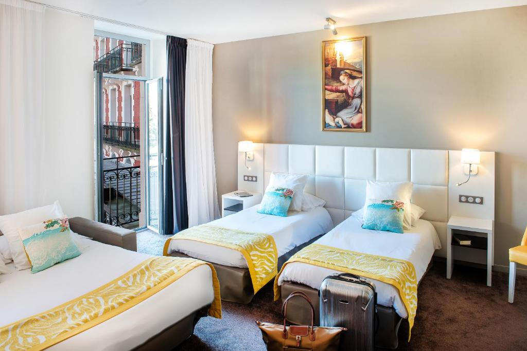 A bed or beds in a room at Grand Hôtel Gallia Chapelle & Nuxe Spa