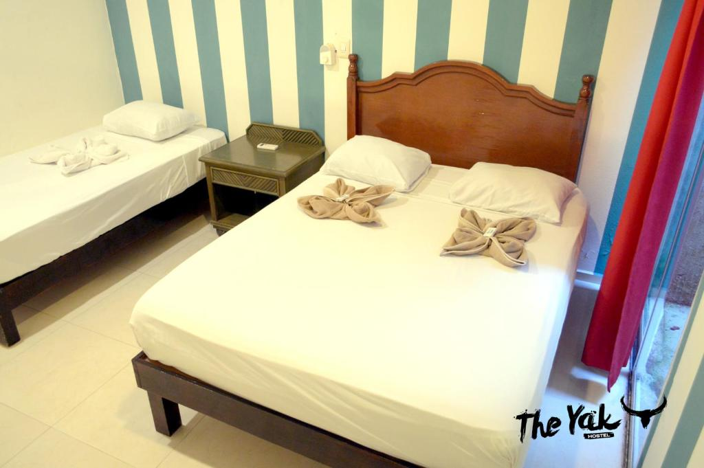 A bed or beds in a room at The Yak Hostel