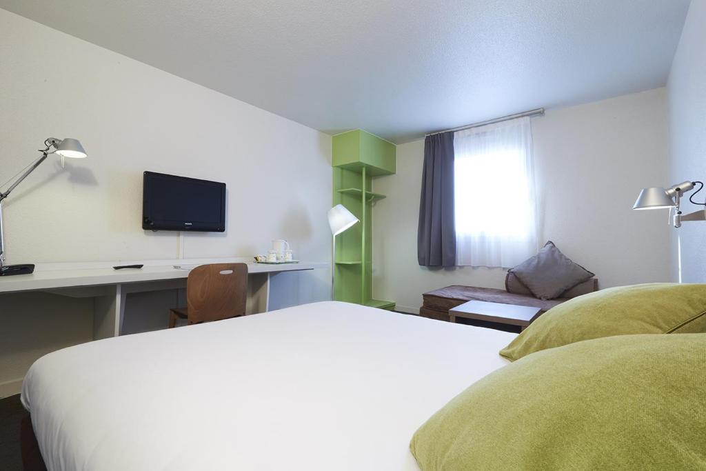 A bed or beds in a room at Campanile Blanc-Mesnil