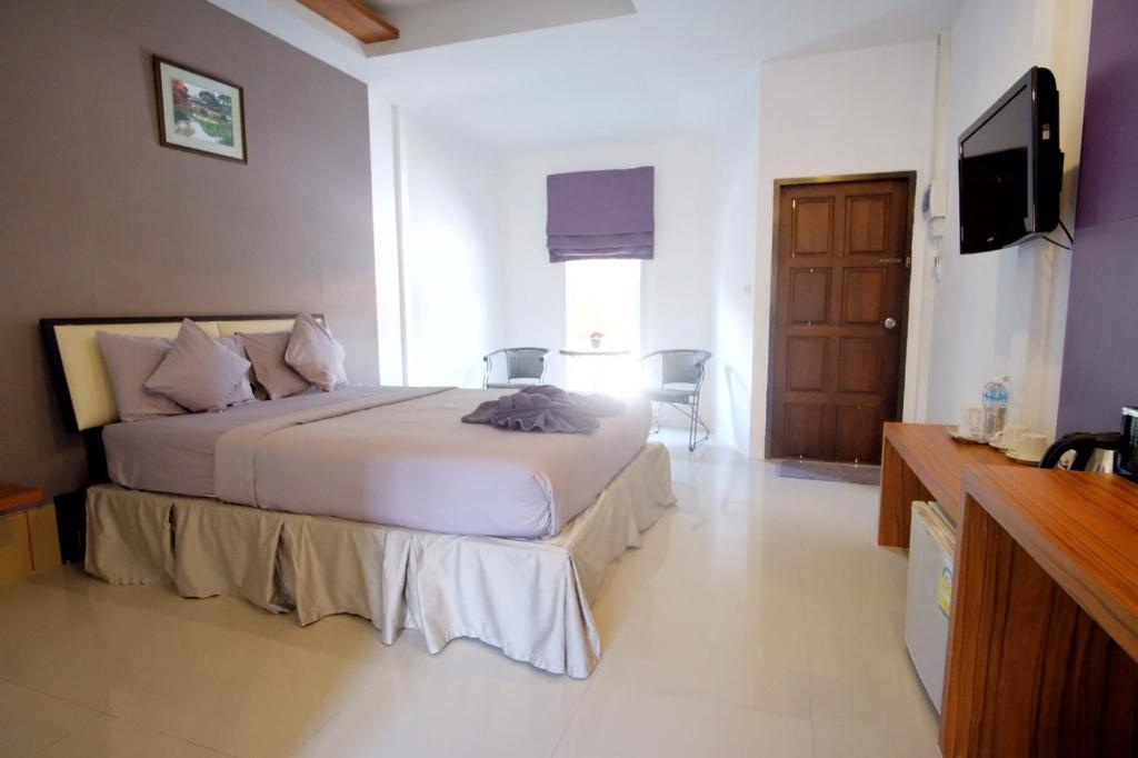 A bed or beds in a room at At Lamai Resort