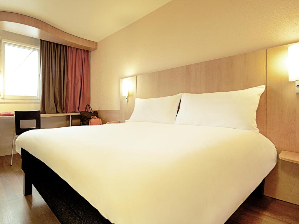 A bed or beds in a room at Hotel ibis Braga