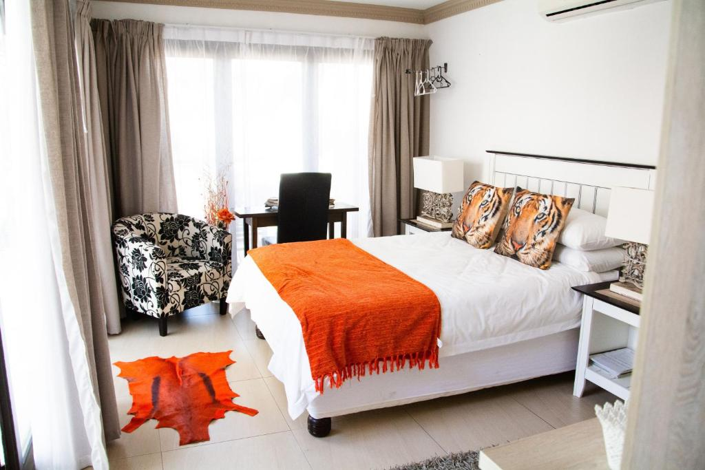 A bed or beds in a room at Altered Ego Guesthouse
