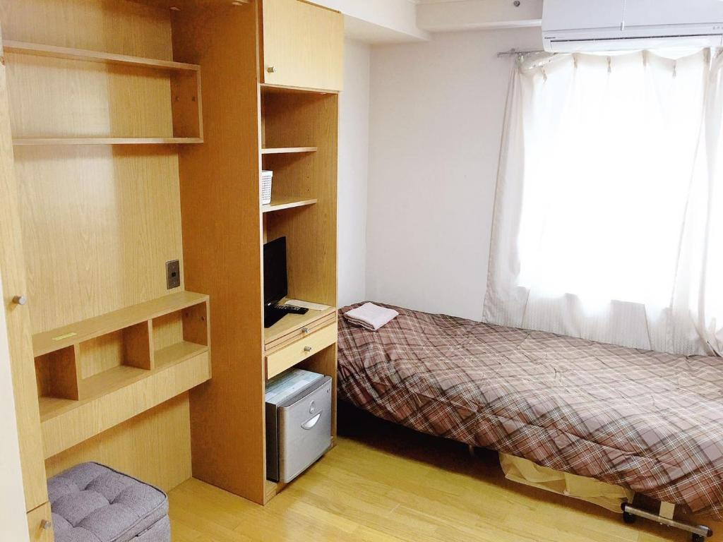 A bed or beds in a room at Flower Apartment inn Tokyo Shinjuku West