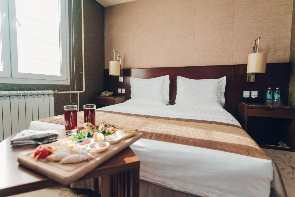 A bed or beds in a room at Soluxe Hotel Almaty