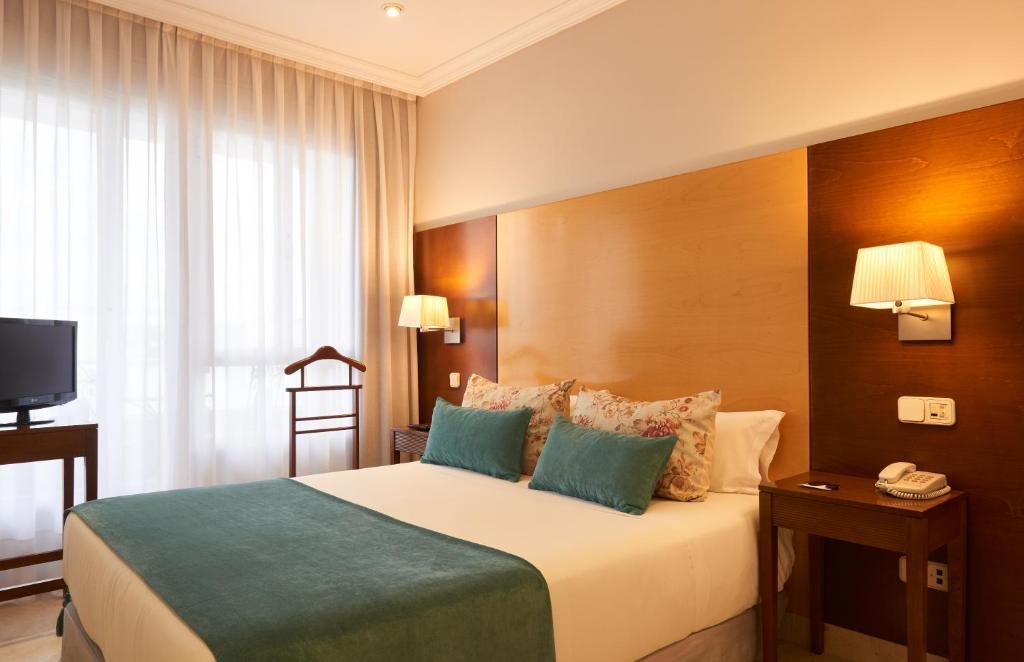 A bed or beds in a room at Suites Barrio de Salamanca