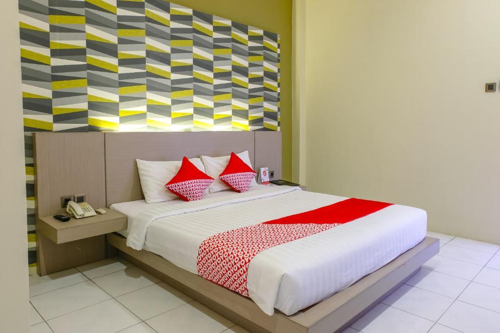 Un pat sau paturi într-o cameră la OYO 972 Griya Asri Hotel Mataram