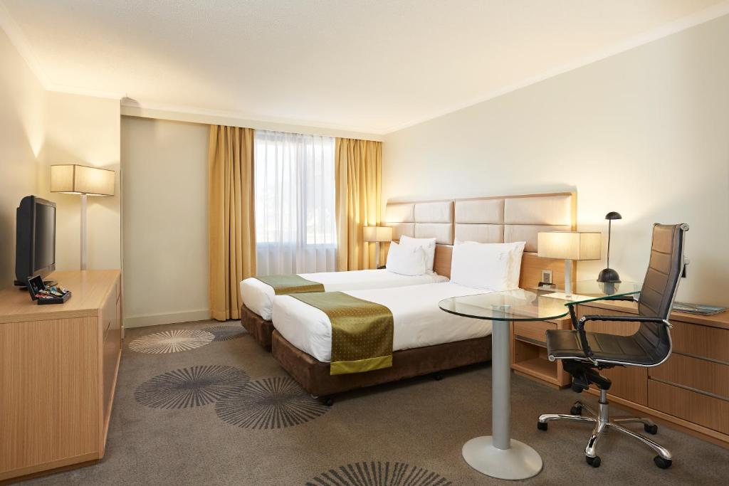 A bed or beds in a room at Holiday Inn Parramatta