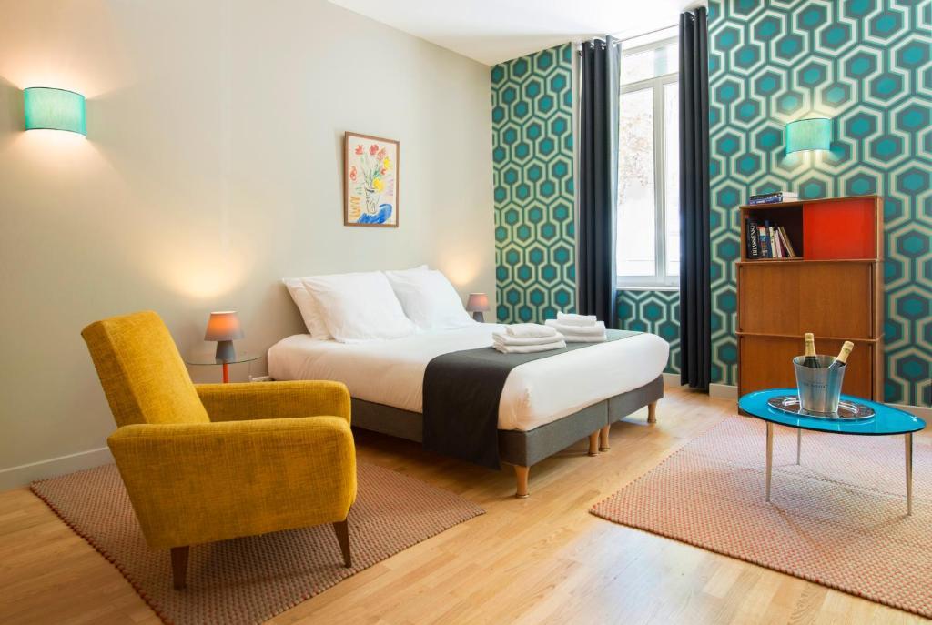 A bed or beds in a room at Suites & Hôtel Helzear Champs-Elysées