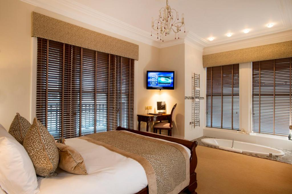 A bed or beds in a room at The Clarence Boutique Hotel