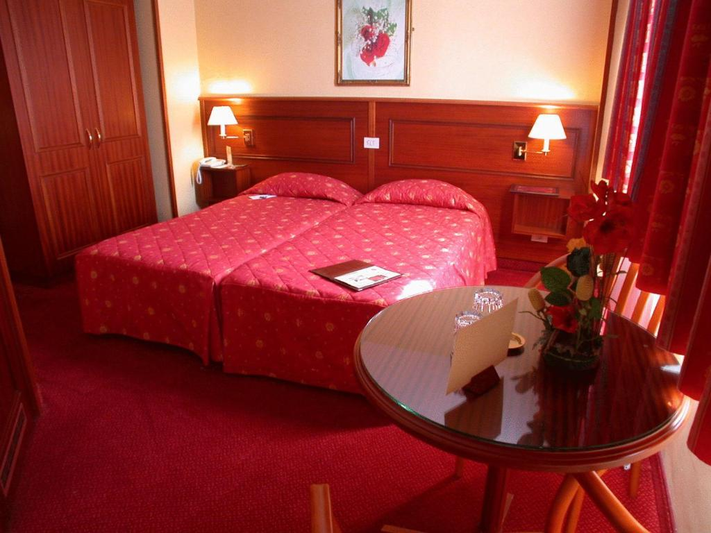 A bed or beds in a room at Logis Hôtel Hamiot